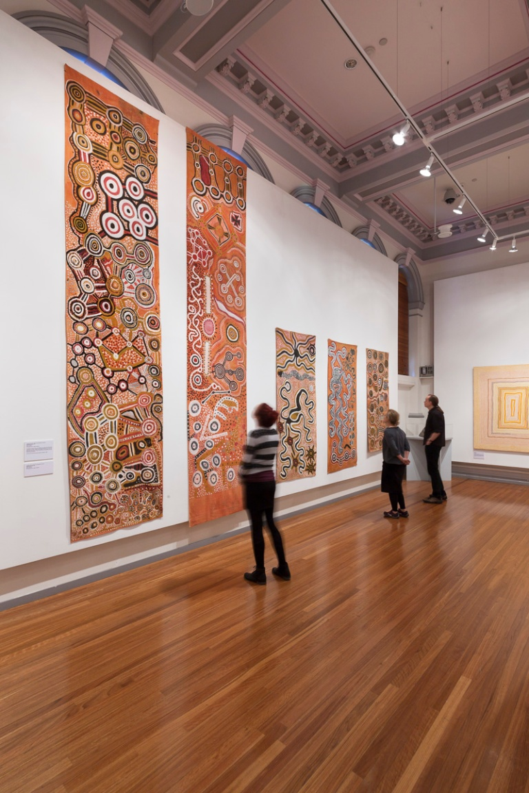 Installation view, Warlayirti: The Art of Balgo at RMIT Gallery. Photo Mark Ashkanasy, 2014. (extreme far right) A group of men, names and associations not given  Assembly banner 1981  Paint on calico 400.0 x 89.0 cm St Theresa Church, Balgo Collection  and (far right) Balgo men, names and associations not given  Assembly banner 1981  Paint on calico 197.0 x 71.0 cm St Theresa Church, Balgo Collection