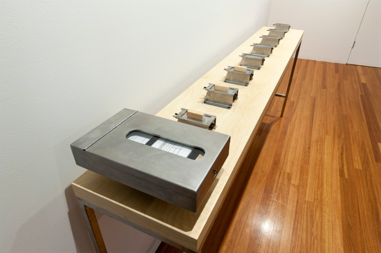 Leisa Shelton, Mapping Australian Media Art 2014–16 performance, desk, chairs, archive cards, rubber stamps, stainless steel archive boxes, custom built plinth 90cm x 236cm x 38cm