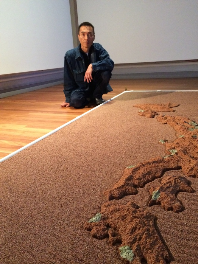 Yutaka Kobayashi with his new work 'Absorption Ripples - Melt down melt away' 2015 Zeolite, Lichen and mixed media, at RMIT Gallery for the exhibition Japanese Art After Fukushima: Return of Godzilla.