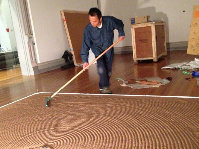 Yutaka KOBAYASHI at RMIT Gallery, working on his piece Absorption Ripples - Melt down melt away 2015 Zeolite, Lichen and mixed media. Image by Evelyn Tsitas