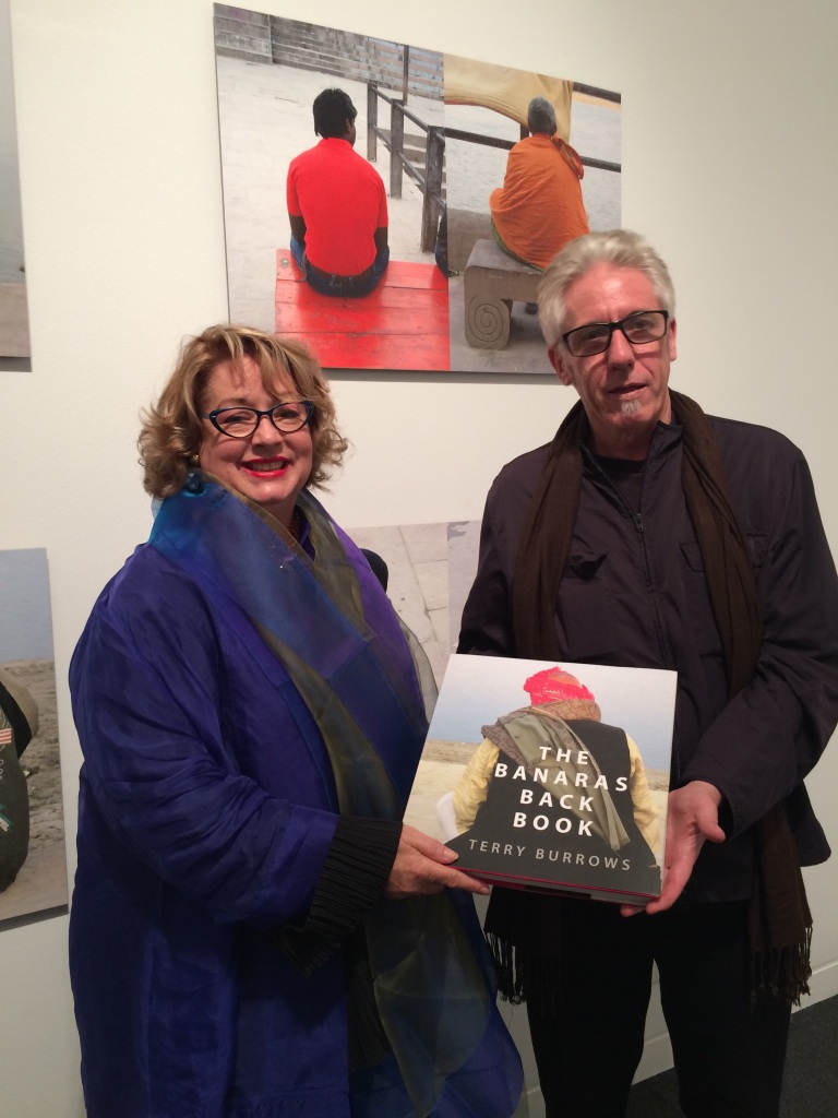 RMIT Gallery Director Suzanne Davies with artist Terry Burrows at his RMIT Gallery exhibition Baccks of Banaras, a curated selection of works from his book which they are holding. Photo: Evelyn Tsitas