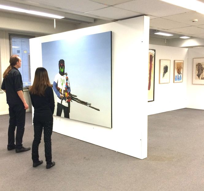 RMIT Gallery Collections Coordinator Jon Buckingham with an RMIT student in the Swanston Street library, in front of Juan Ford's work Degenerator, 2013, oil on linen, 180 x 240cm. Photo Evelyn Tsitas