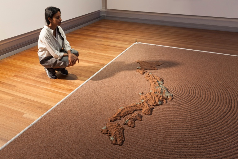 Kaushali Seneviratne at the 2015 RMIT Gallery exhibition Japanese Art After Fukushima: Return of Godzilla, posing next to Yutaka Kobayashi's work 'Absorption Ripples – Melt down melt away' 2015