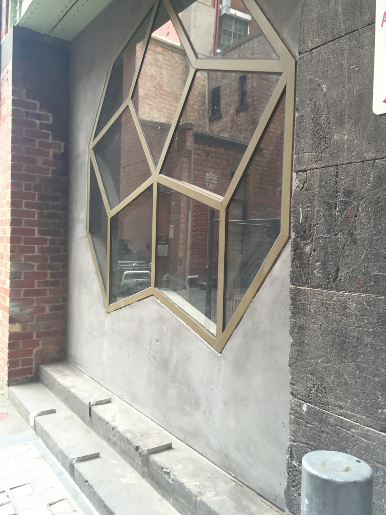 Usually a view to nowhere - the temporarily uncovered window into RMIT Gallery from Rodda Lane.
