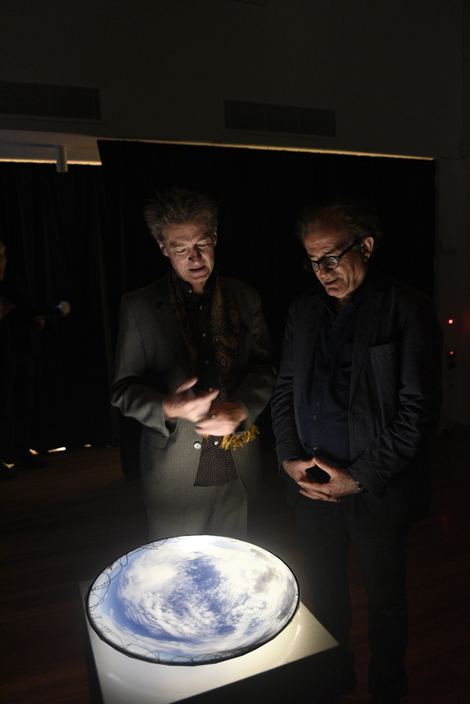 Graeme Miller (left) and Mammad Aidani contemplate the latest Australian based addition of Miller's installation Beheld, which documents sites where stowaways have tragically fallen from planes. This was taken at Sydney airport, which was the site of such an accident in 1970. Photo; Vicki Jones Photography, 2015.