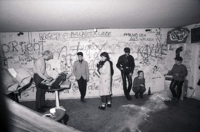 Caption: Alex Hacke playing with Kiddy Citny (in the band Sprung aus den Wolken) to a small audience: Silvie Langenfeld (3rd from left), Blixa Bargeld (Einstürzende Neubauten, 4th from left), Risiko, Berlin, 1981, photo Anno Dittmer, Geniale Dilletanten exhibition.