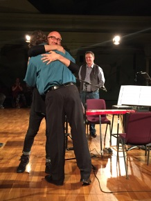 Following the world premiereComposer Timothy McCormack hugs musician Peter Neville (in blue shirt) and Daryl Buckley looks on.